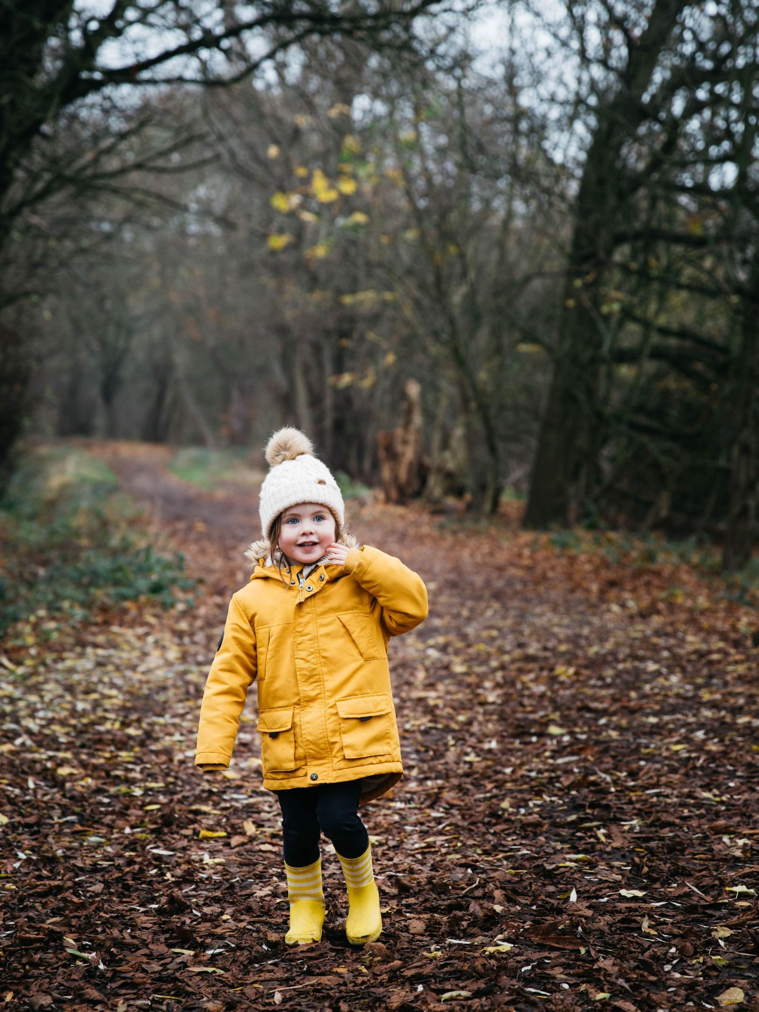 autumn walk in forest with small girl in yellow jacket