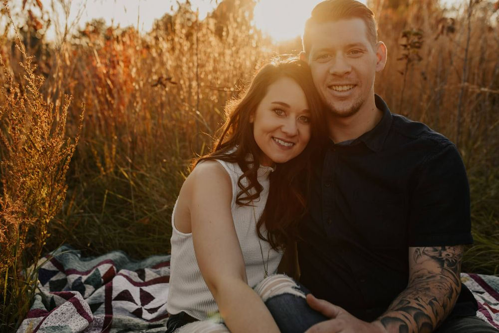 Engagement Photography Kansas City Blog Couple sitting on blanket in grassy field with sun setting behind