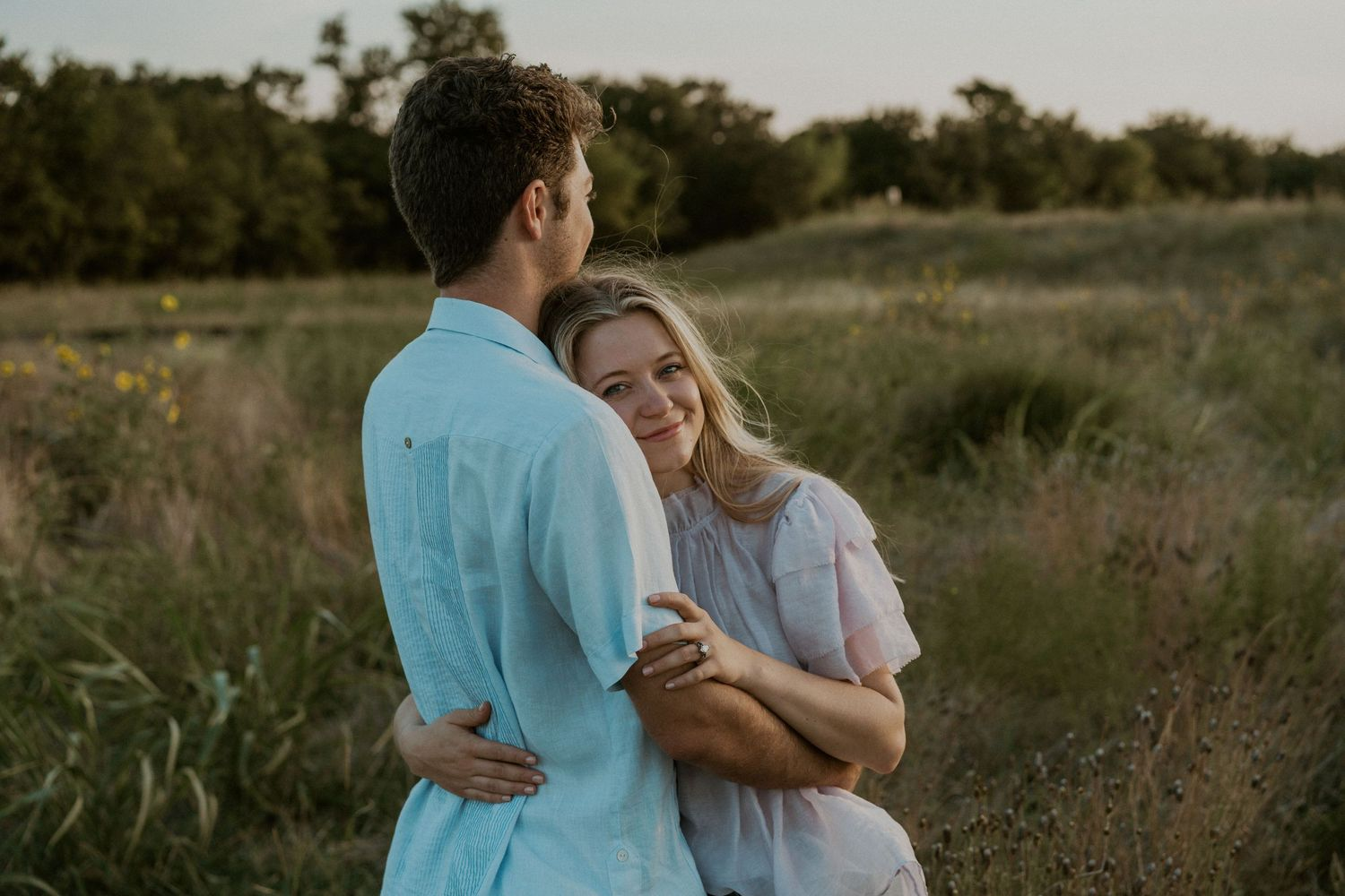 photo taken by Kelsie Burke Photography of a Couple in Austin, TX snuggled up in a field
