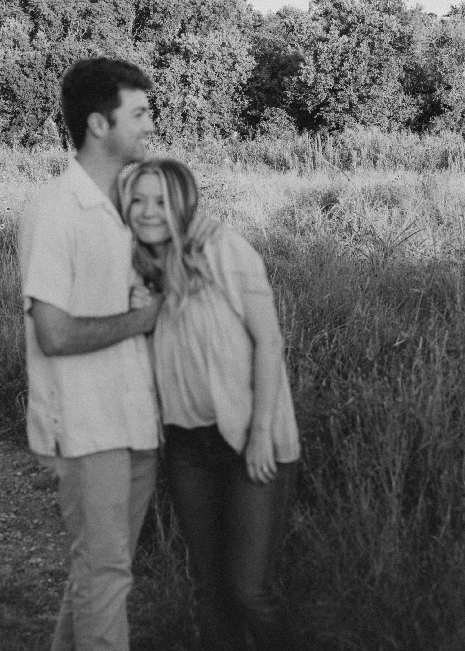 Blurry photo of a Couple in Austin, TX snuggled up in a field