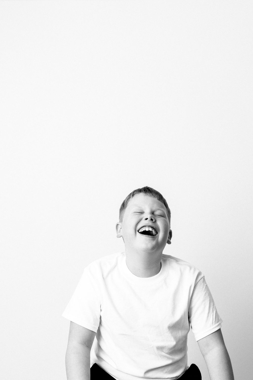 black and white portrait of boy laughing