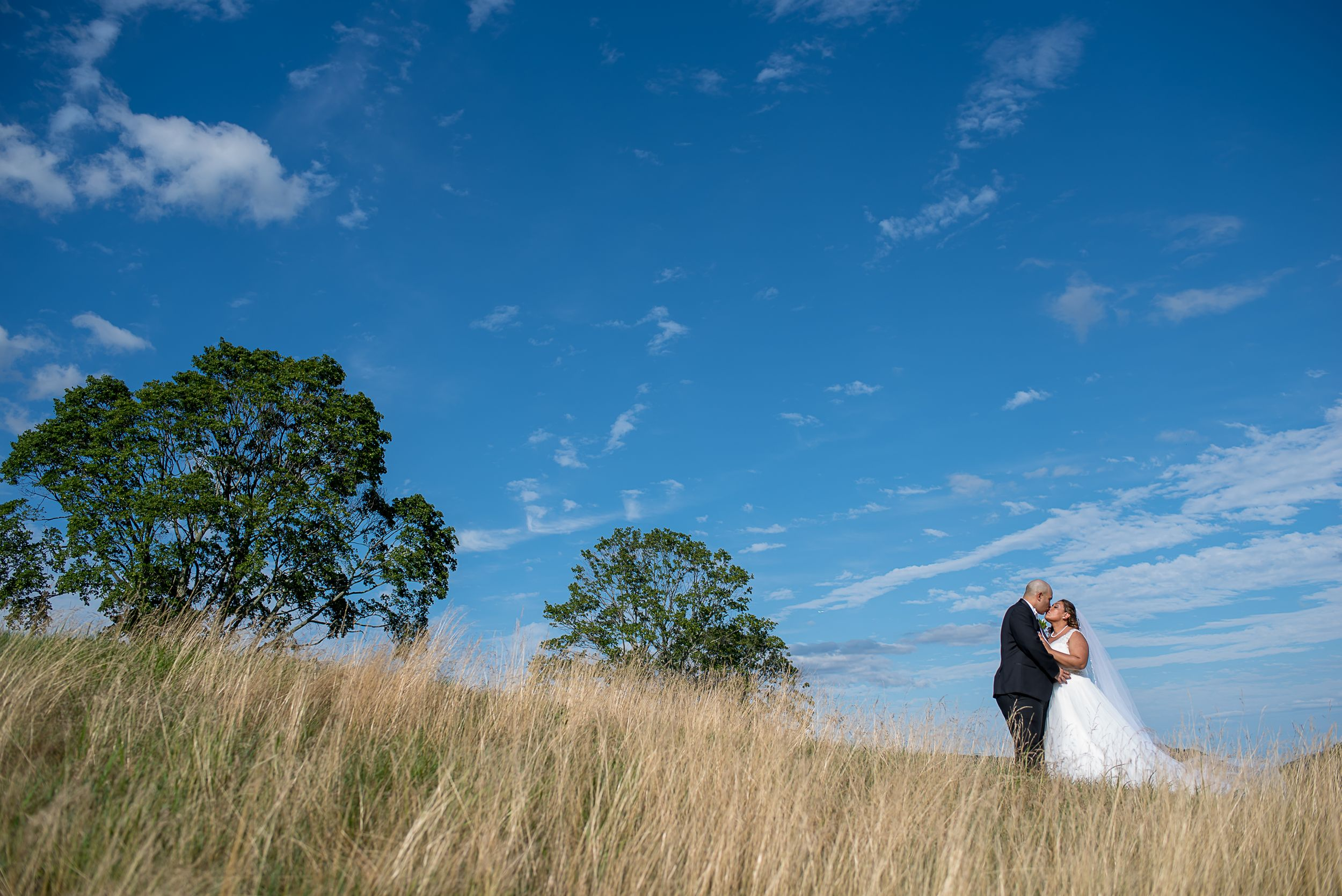 epic photo of wedding couple embracing on hillside on a Northern New Jersey golf course with bright blue sky and clouds