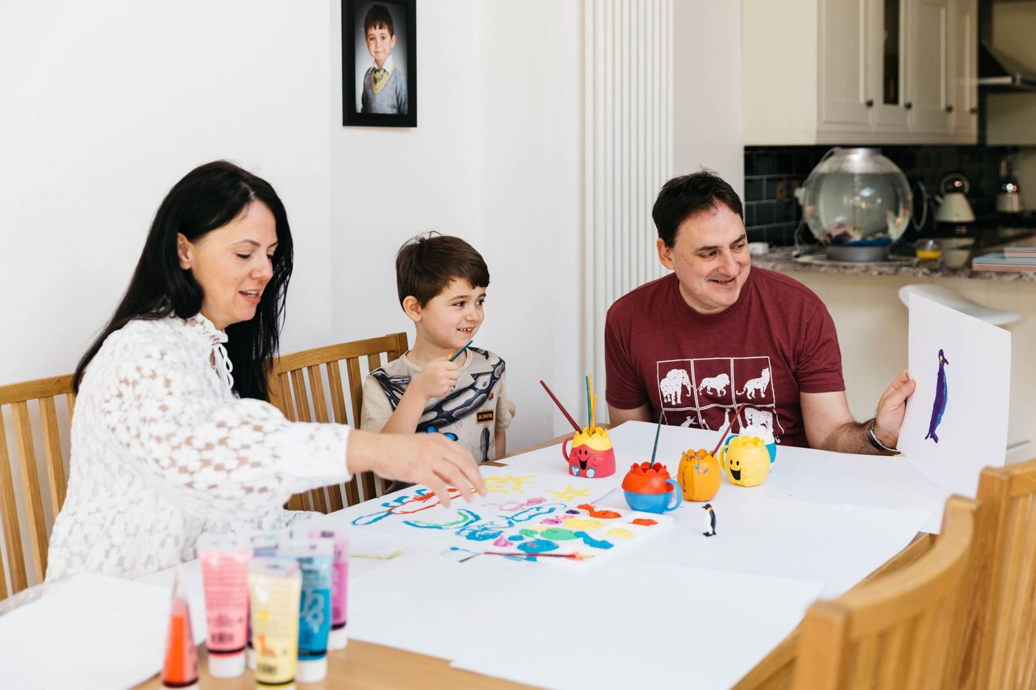 family of three at home with dog painting pictures at table