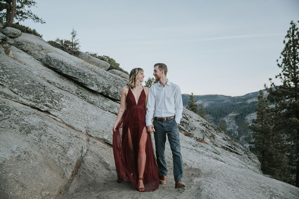 engaged couple walking in yosemite