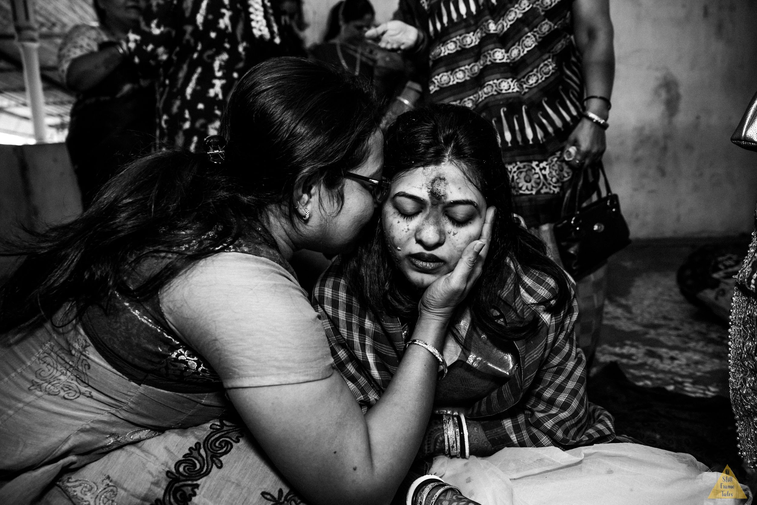 Auntie kissing emotional bride on her haldi ceremony in a black & white picture