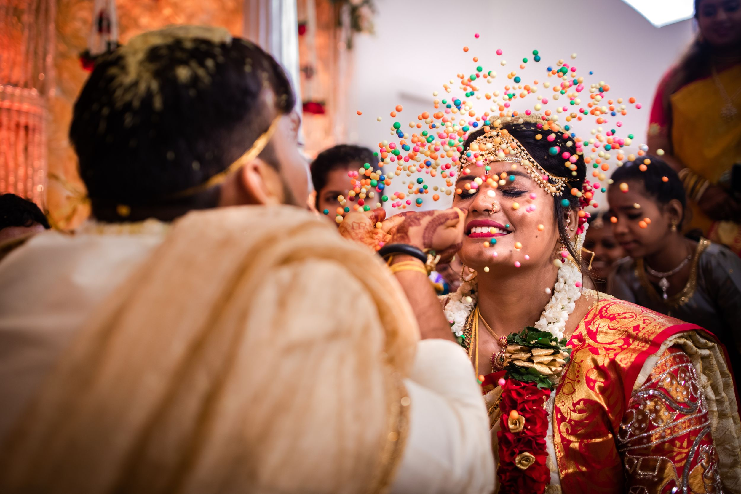Groom showering on bride at Indian wedding ritual