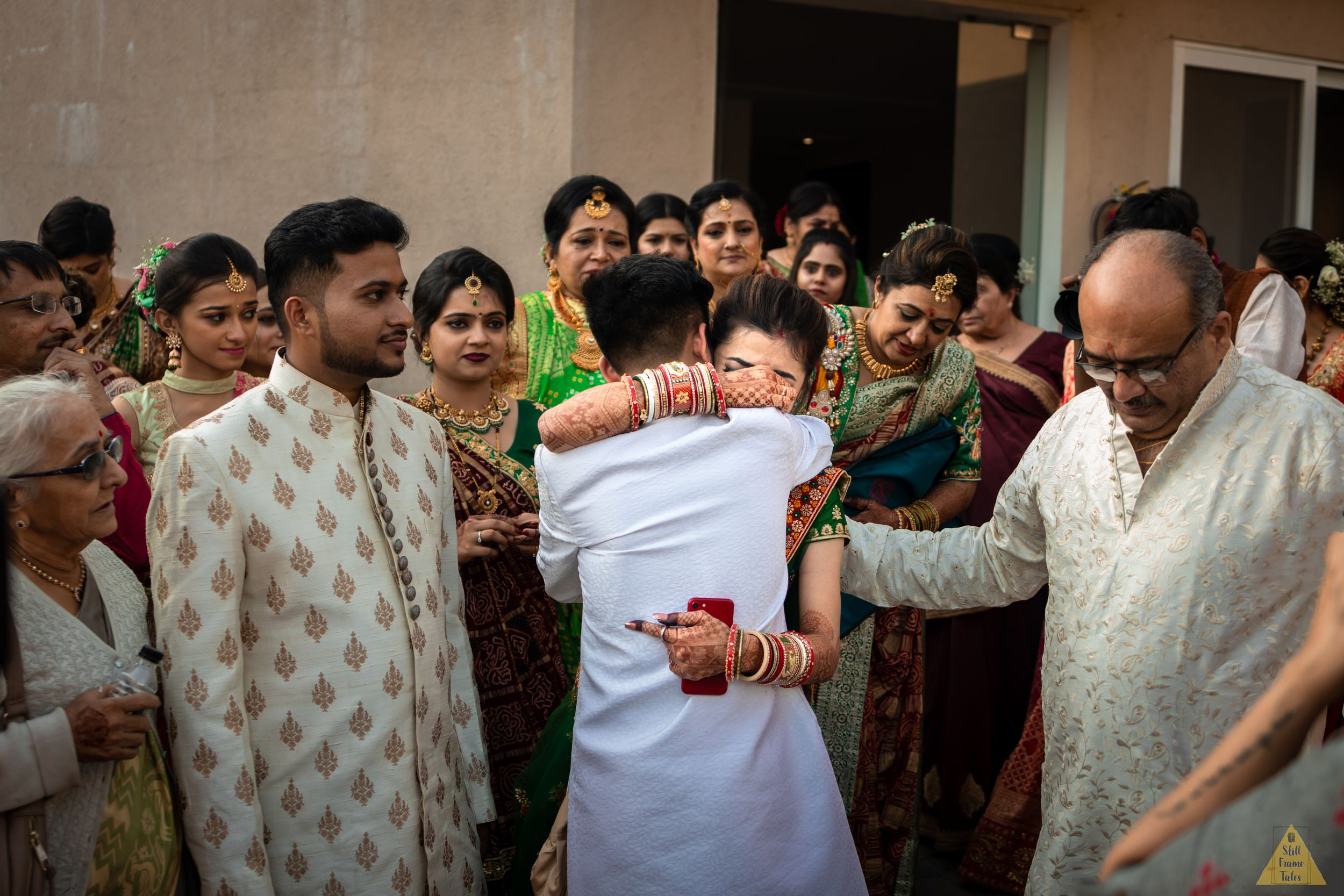 Bride tightly hugging brother during her vidai in a destination Indian wedding