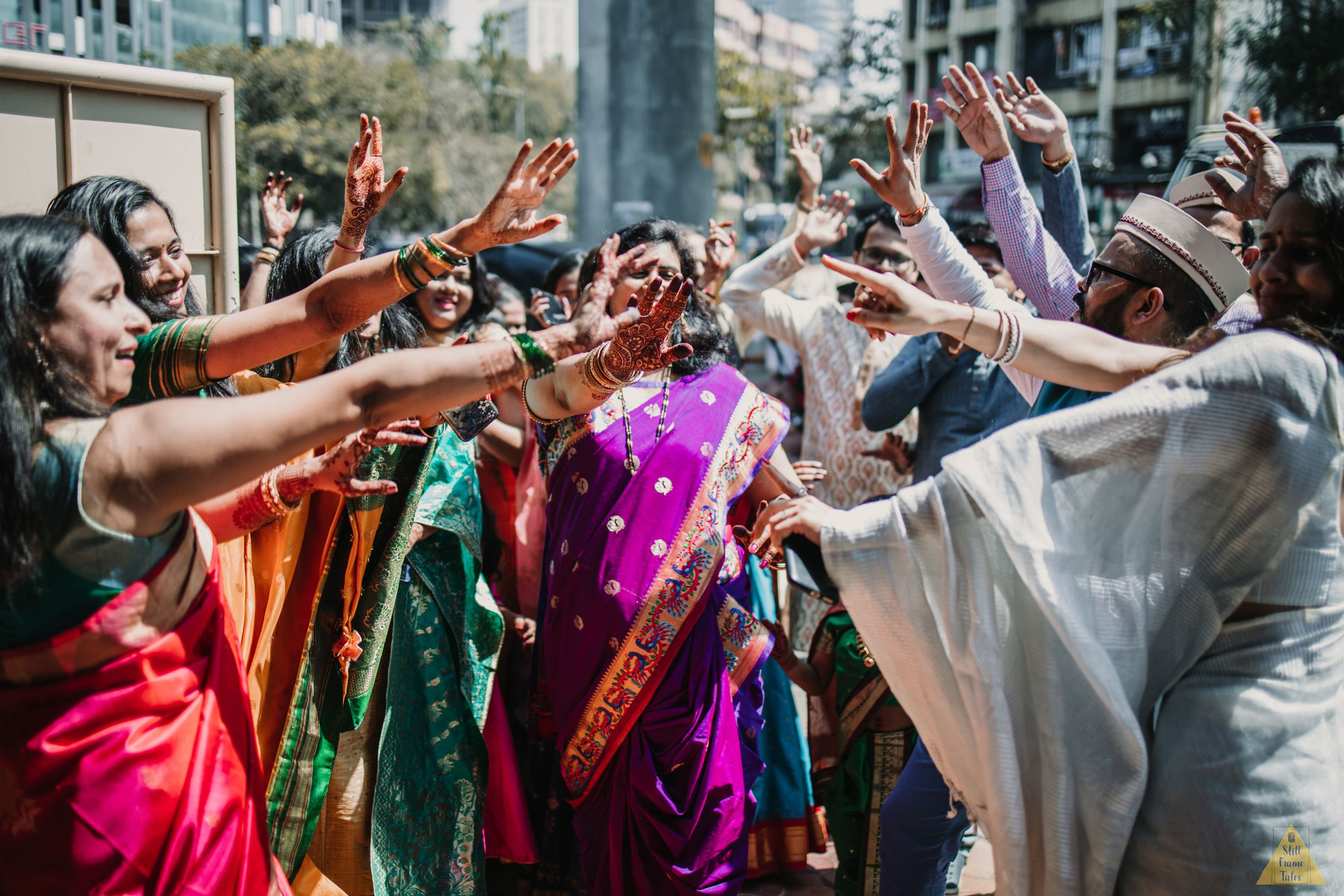 Friends & family dancing together in sun light during a Indian wedding