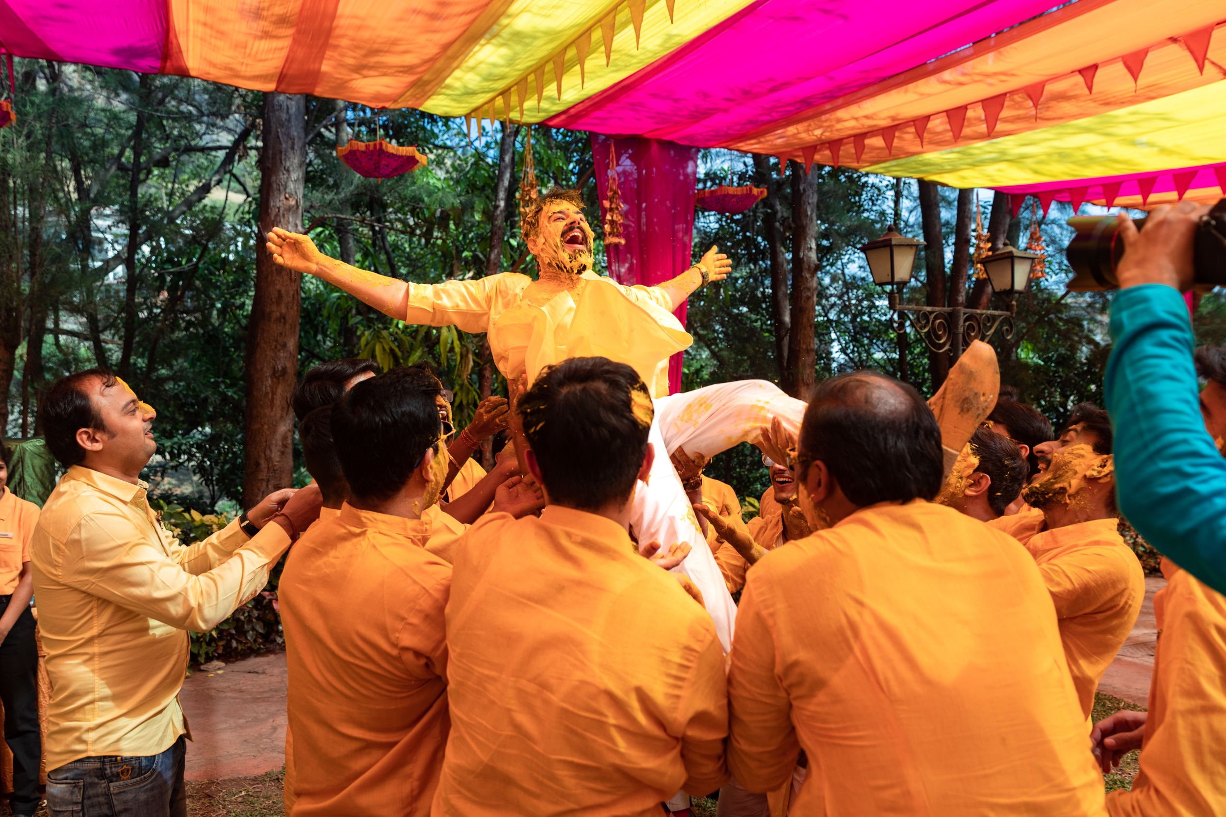 Friends & cousins tossing groom up in the air on a destination luxury wedding haldi