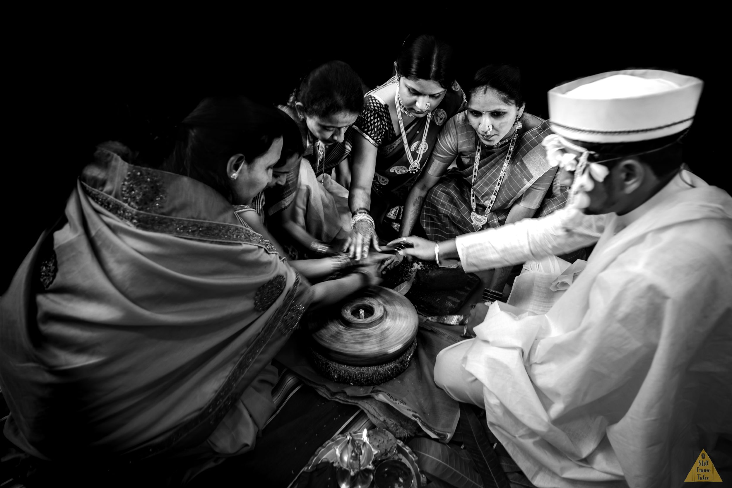 Family & groom performing wedding day ritual in a black & withe picture