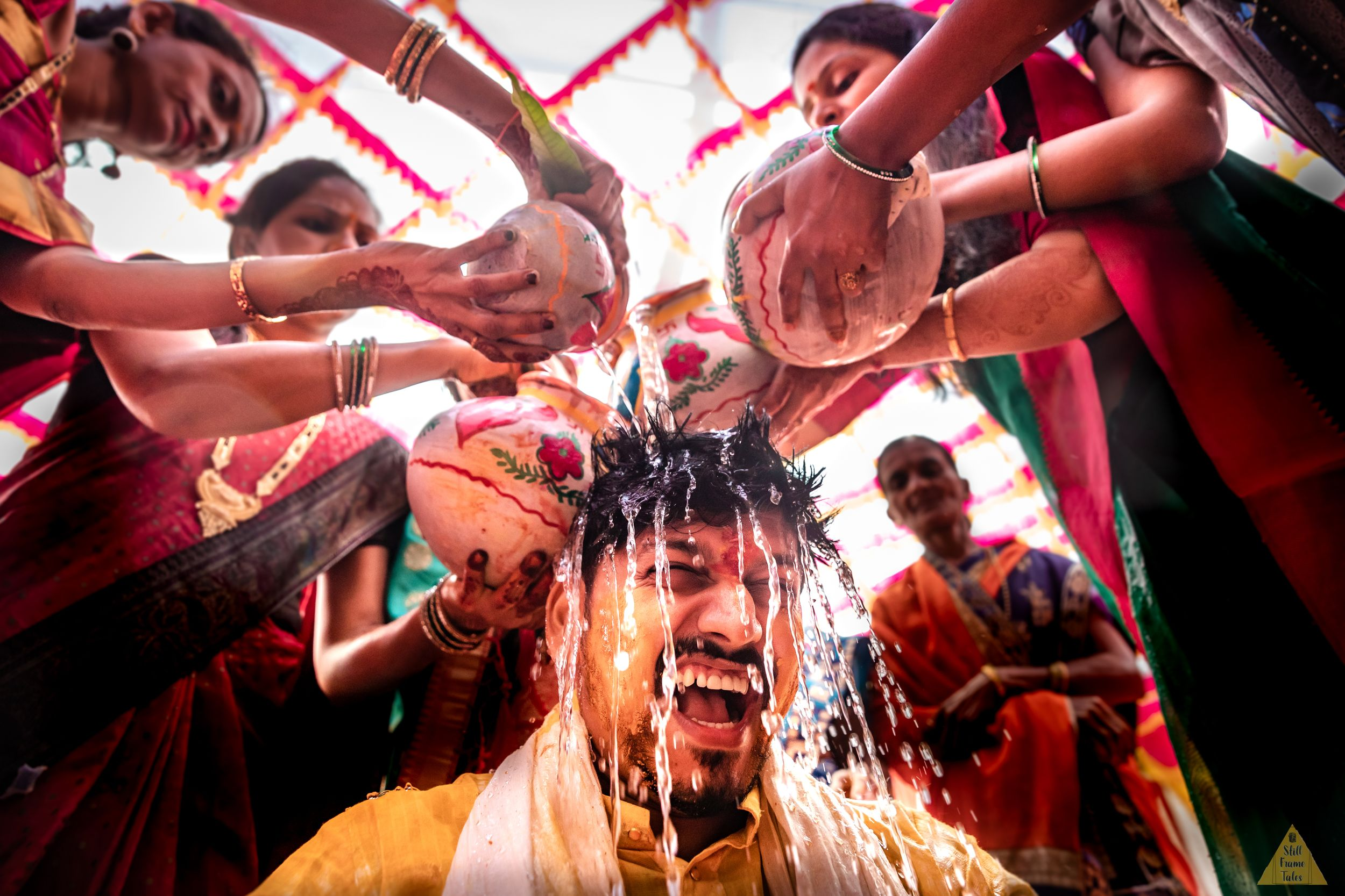 Family showering chilled water on groom during haldi rituals