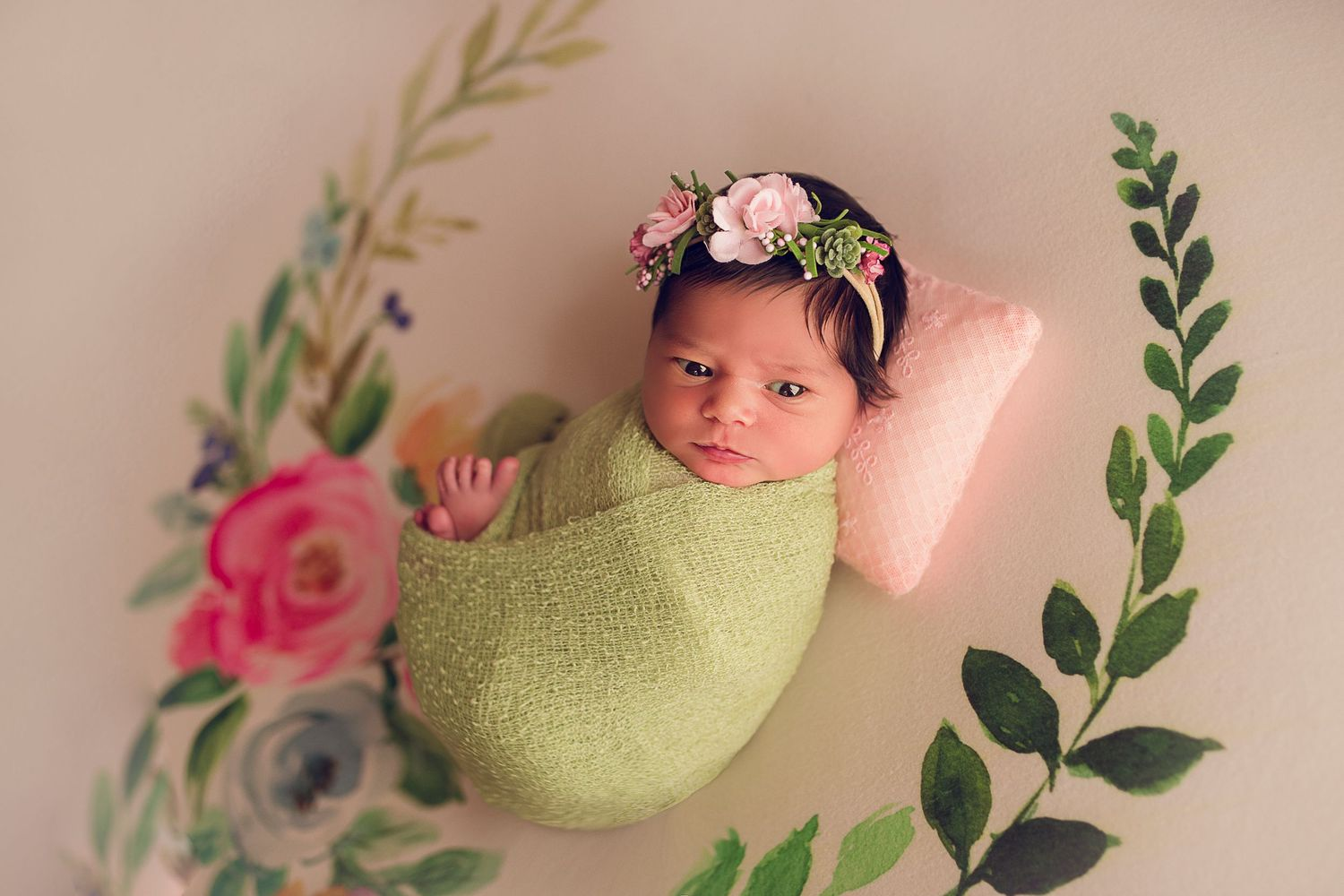 newborn baby wrapped in green with floral crown