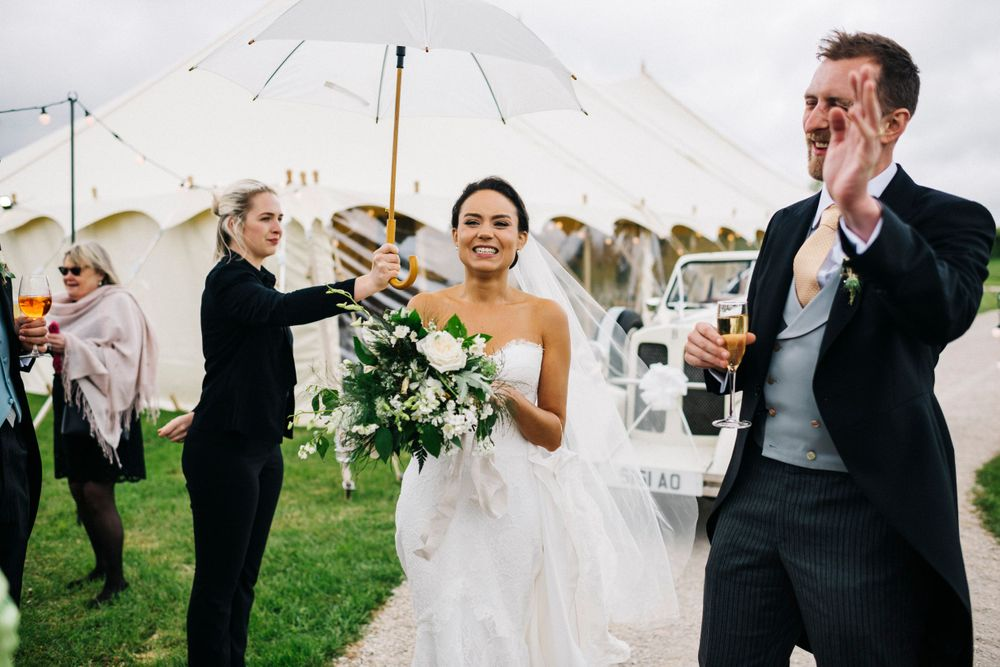 Rainy wedding day, wedding umbrella, bride and groom arrival, classic wedding, marquee wedding, Suzanne Nevill dress