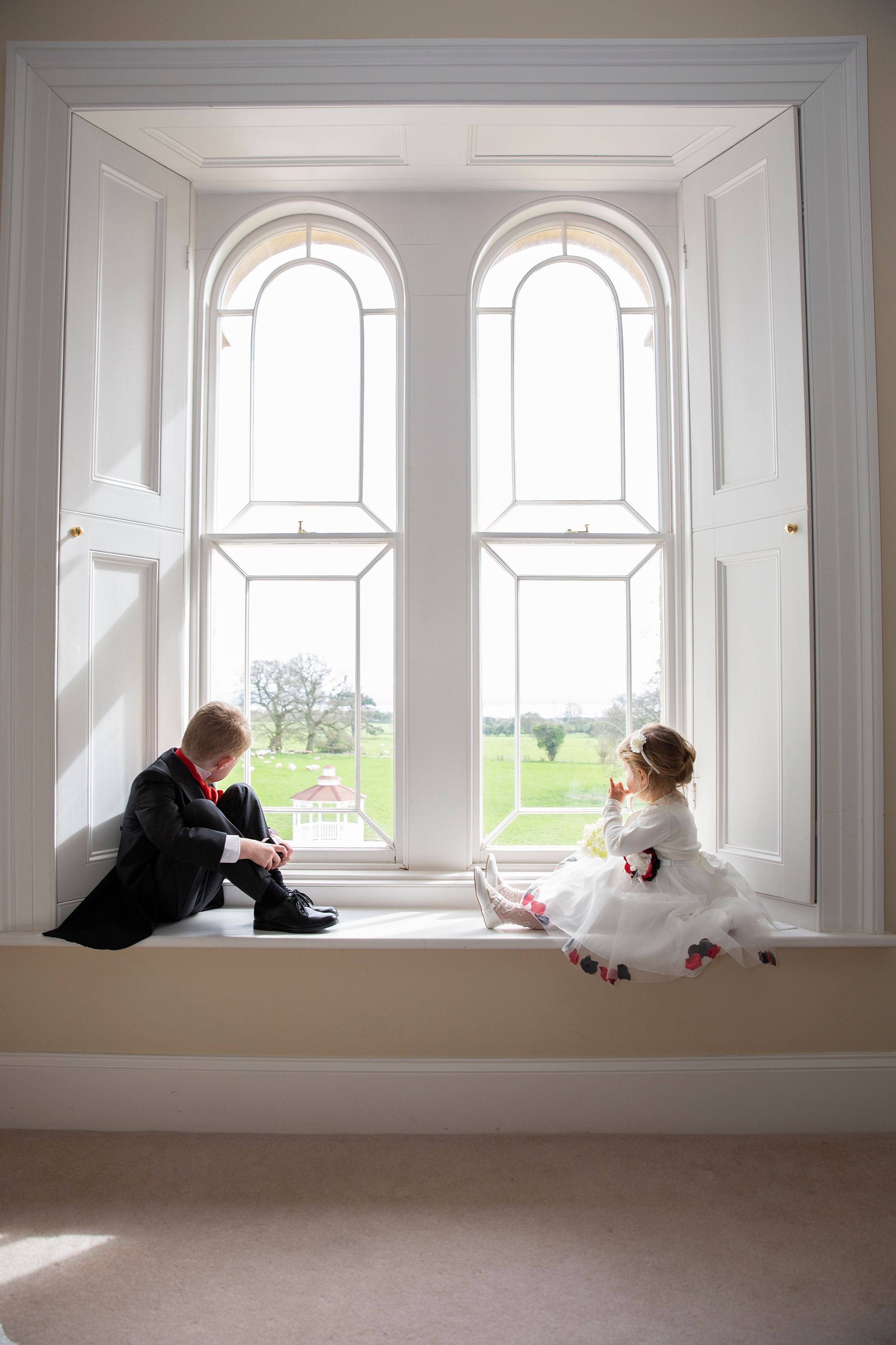 lovely moment page boy and flower girl sitting in the window at St Tewdrics House Chepstow