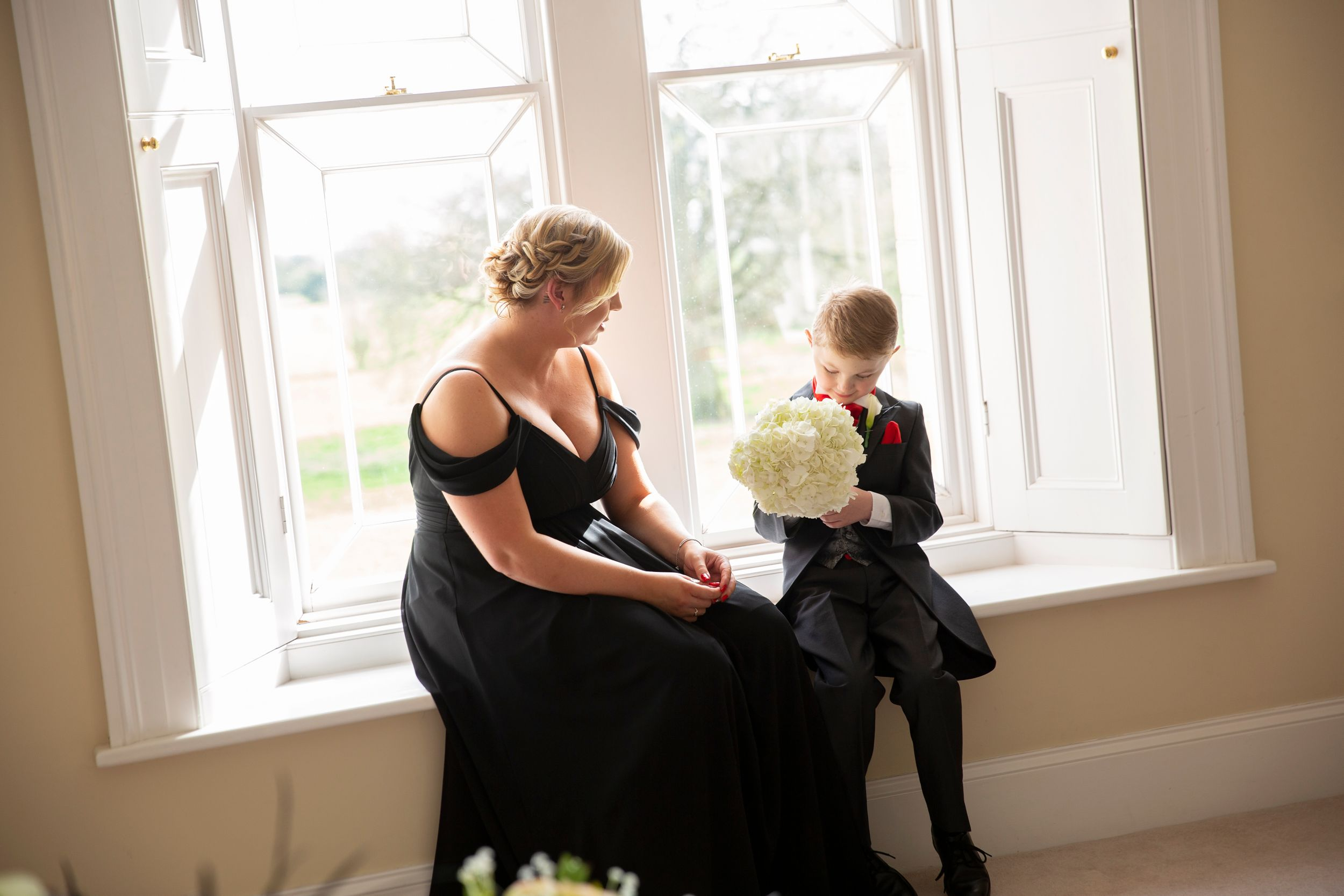 charming candid moment bridesmaid with her son at window in St Tewdrics Wedding