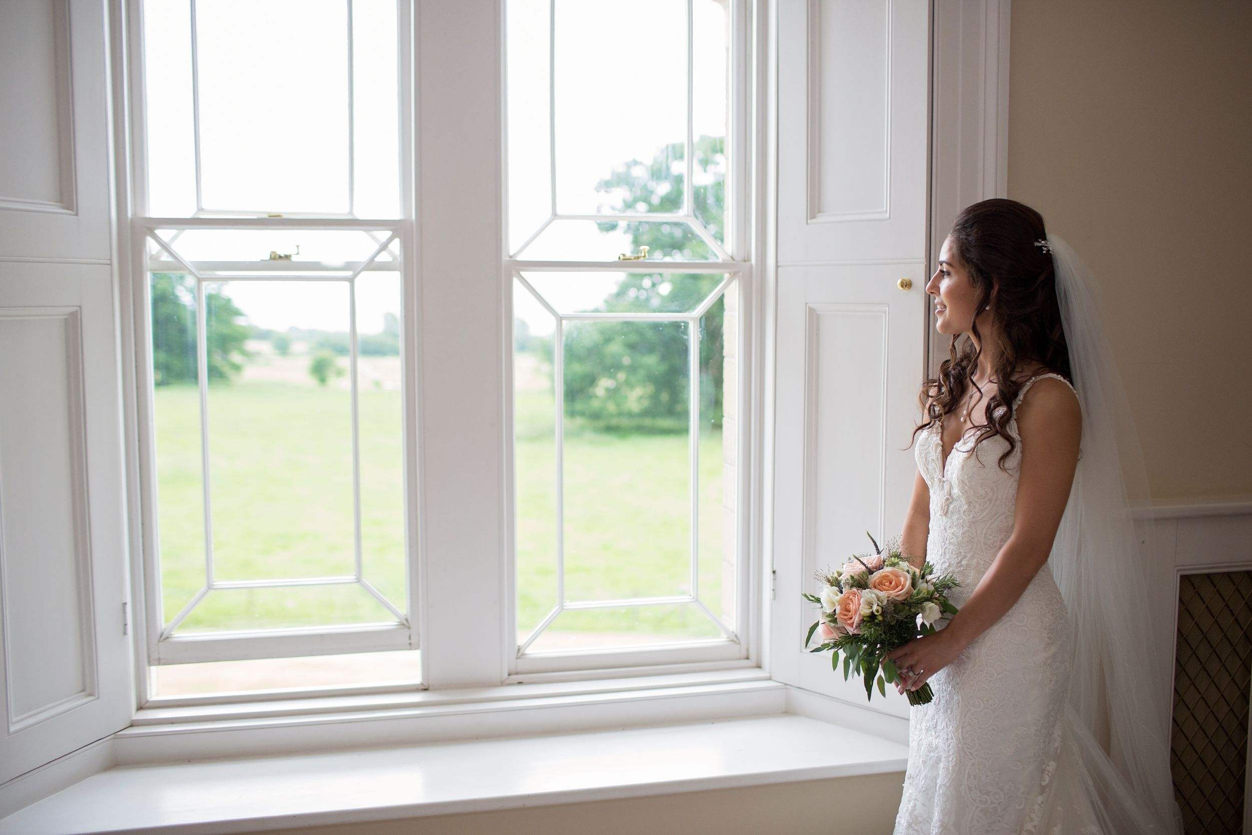 Bride gazing out window at St Tewdrics House