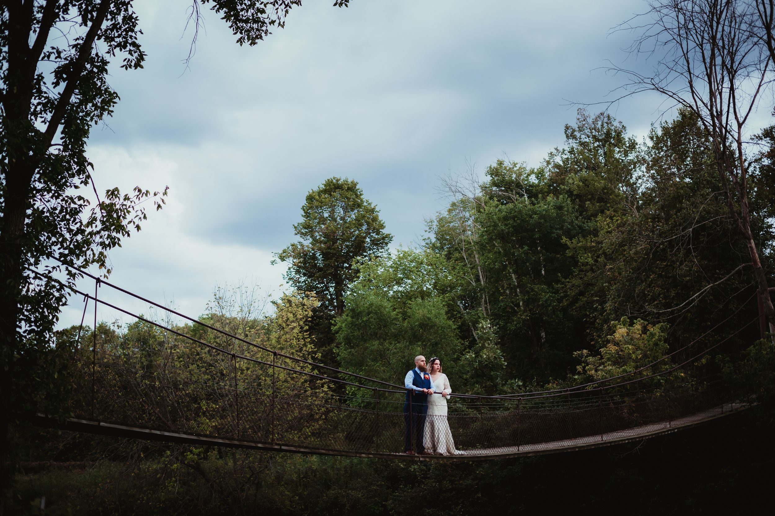 Man and woman in wedding attire standing in the middle of a swinging cable rope bridge.