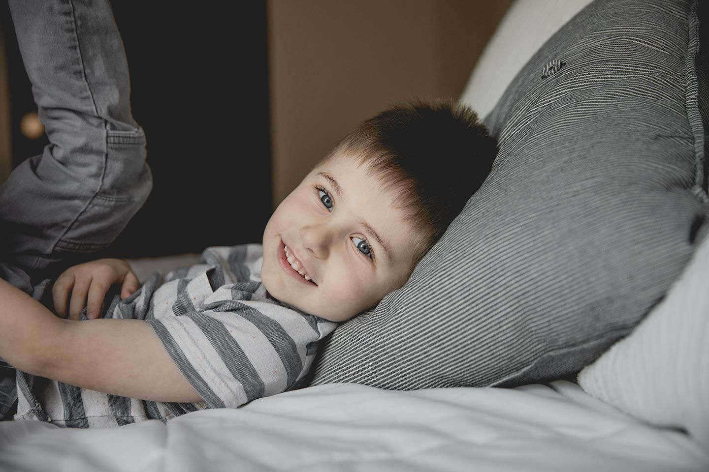 little boy laying on bed smiling