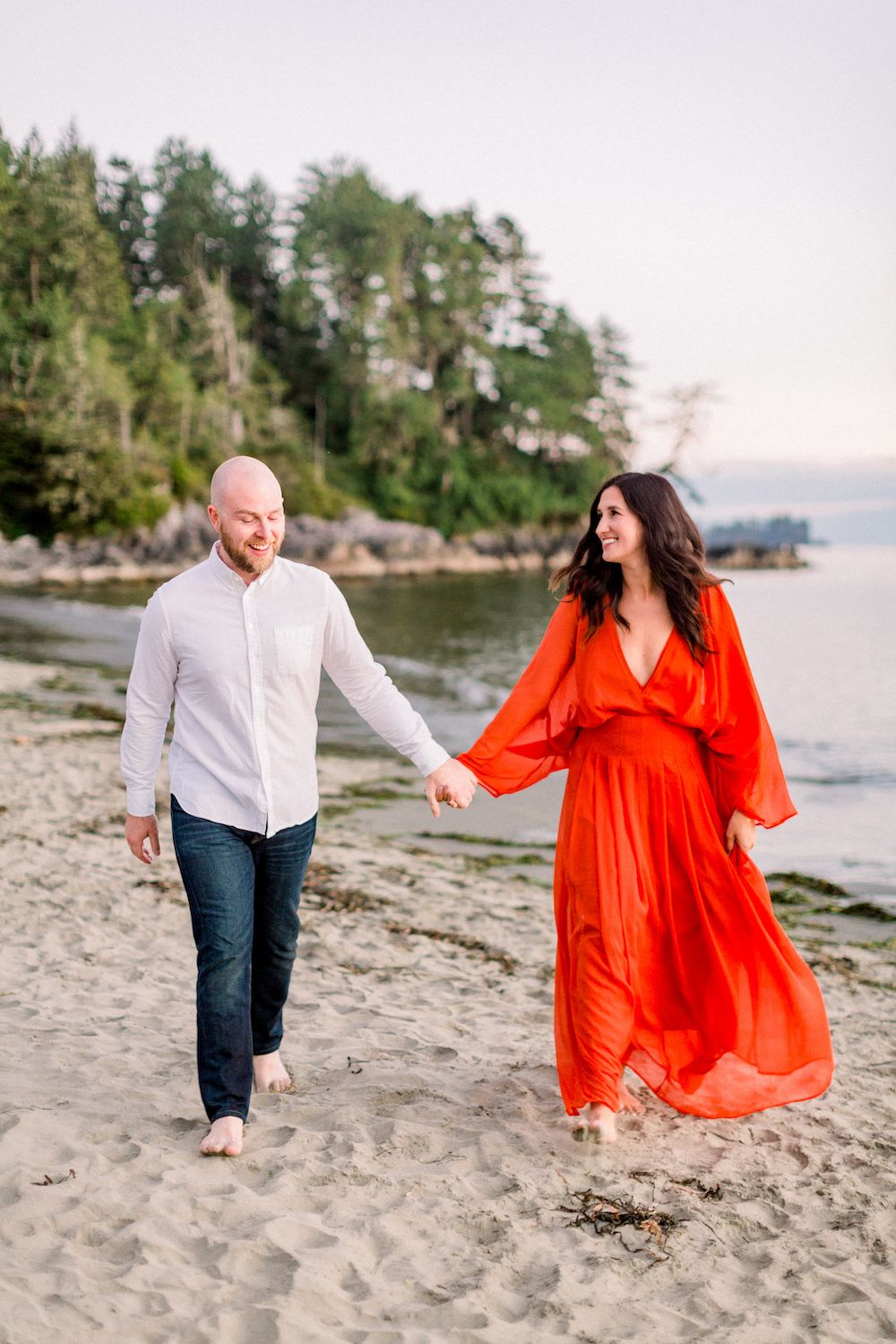 Couple holding hands and walking on the beach in Tofino