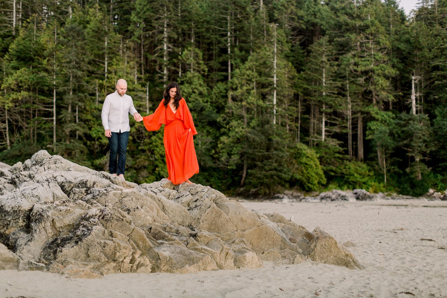 Couple holding hands during engagement session on the beach