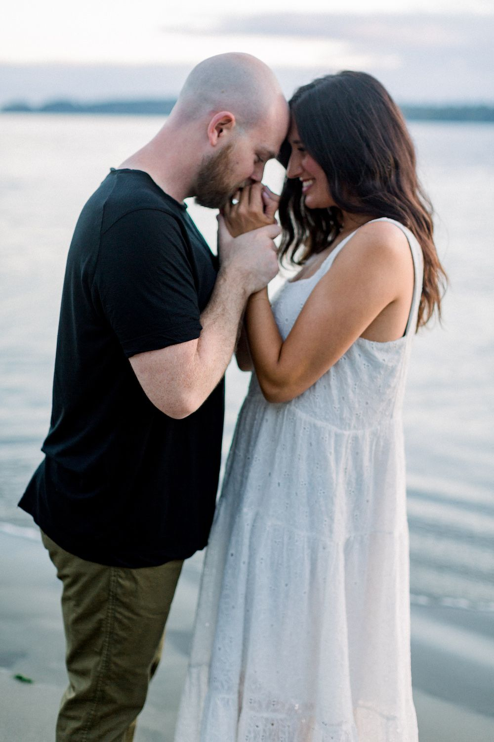 Boyfriend kissing girlfriend's hands during engagement session on the beach