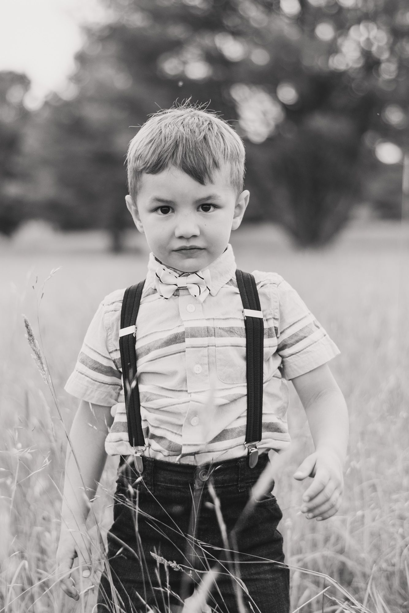 Little boy in suspenders with somber expression in field in black and white in Clarion Pennsylvania