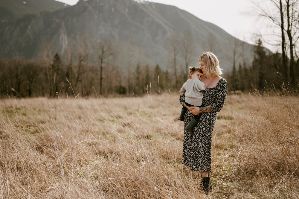 Motherhood portrait by Tiffany Kelterer of mom holding toddler daughter in field in front of Mt Si Washington