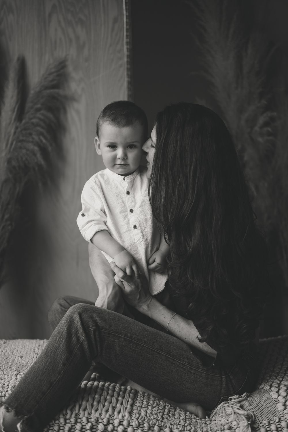 Black and White motherhood portrait by Tiffany Kelterer of mom with toddler boy and he's looking directly at the camera