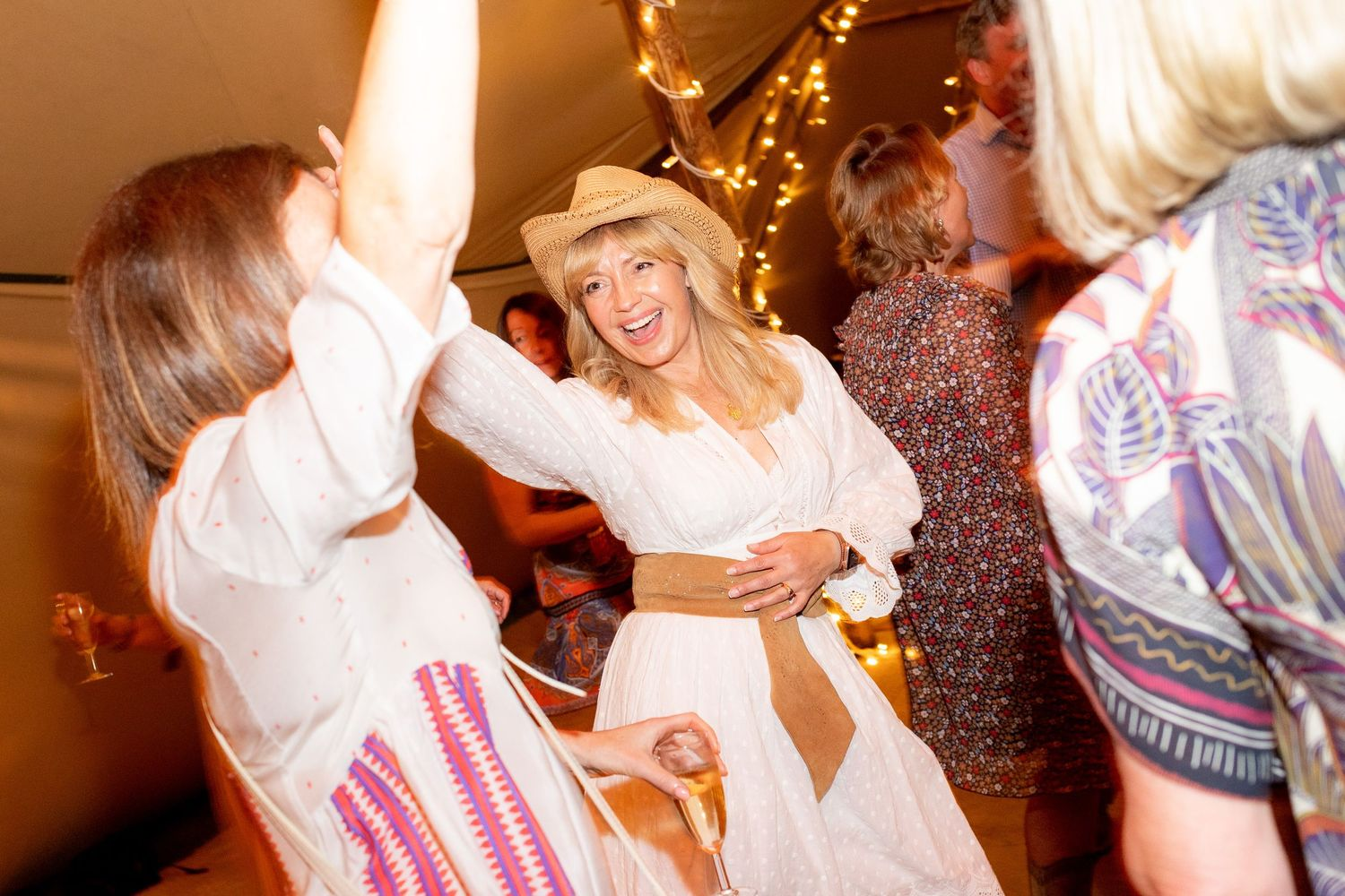 A woman wearing a white dress and cowboy hat dances in a teepee at a party - Party photography