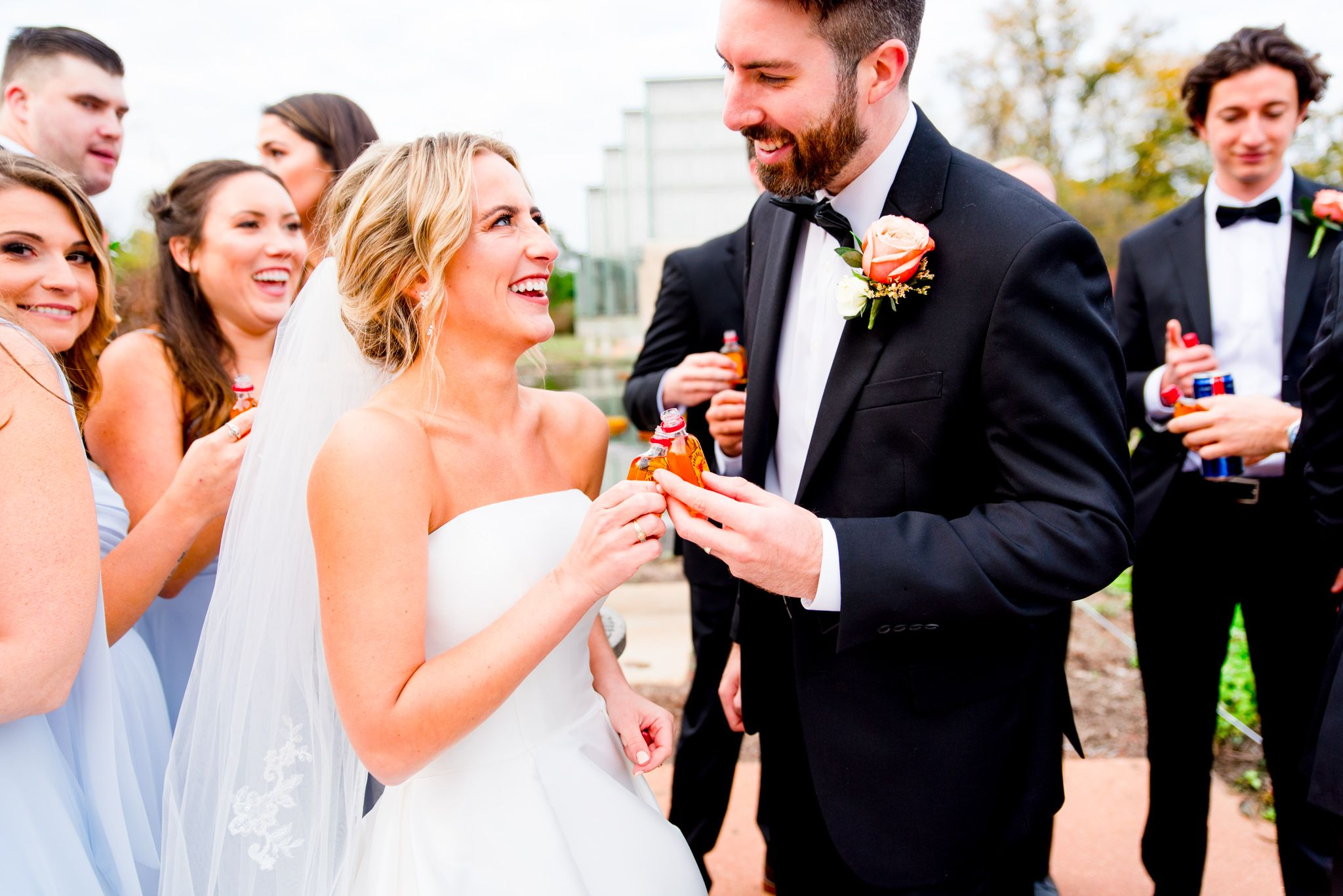 bride and groom smiling at each other, clinking mini fireball bottles together on wedding day