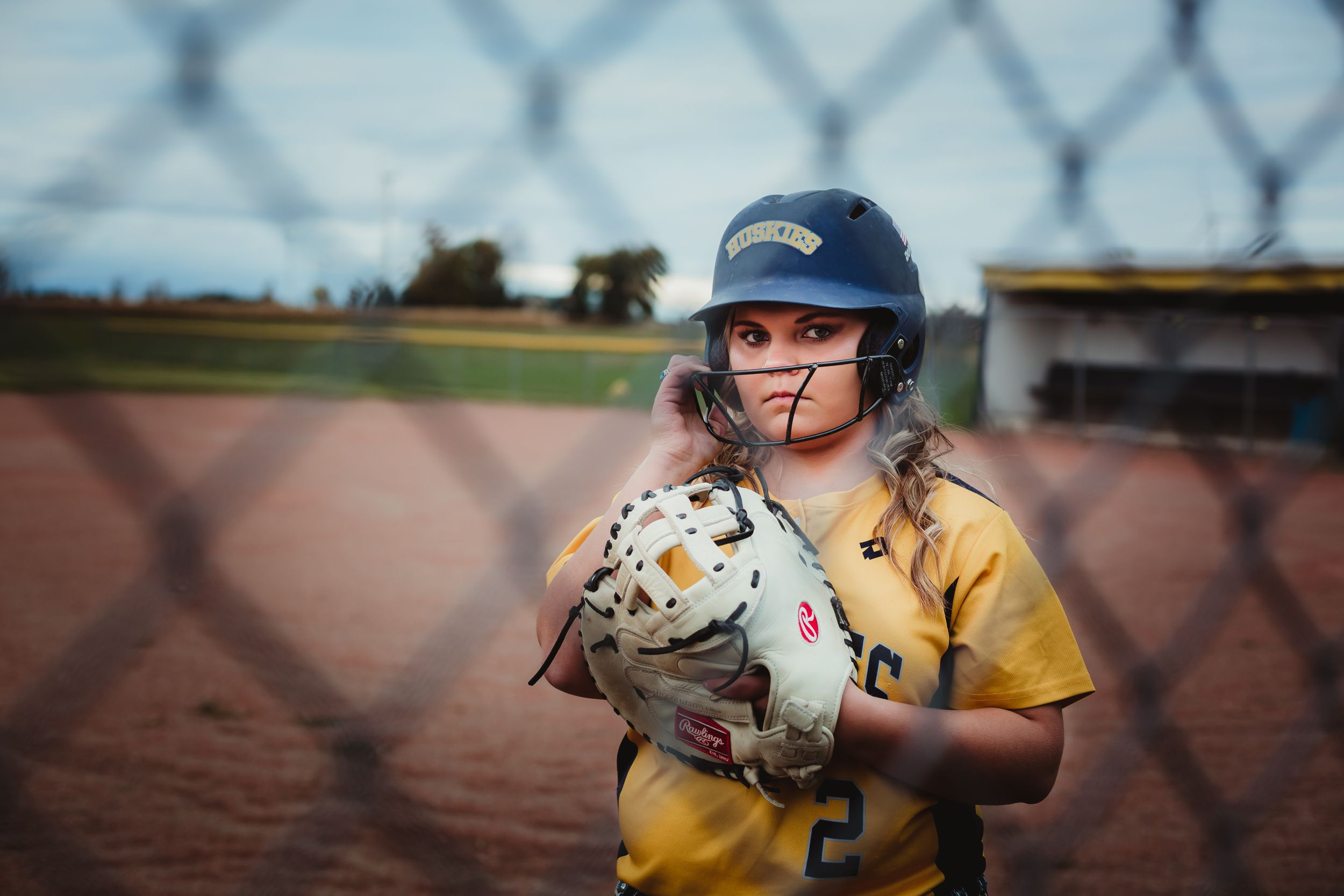 High school senior girl with glove and helmet standing on a softball field behind the fence.