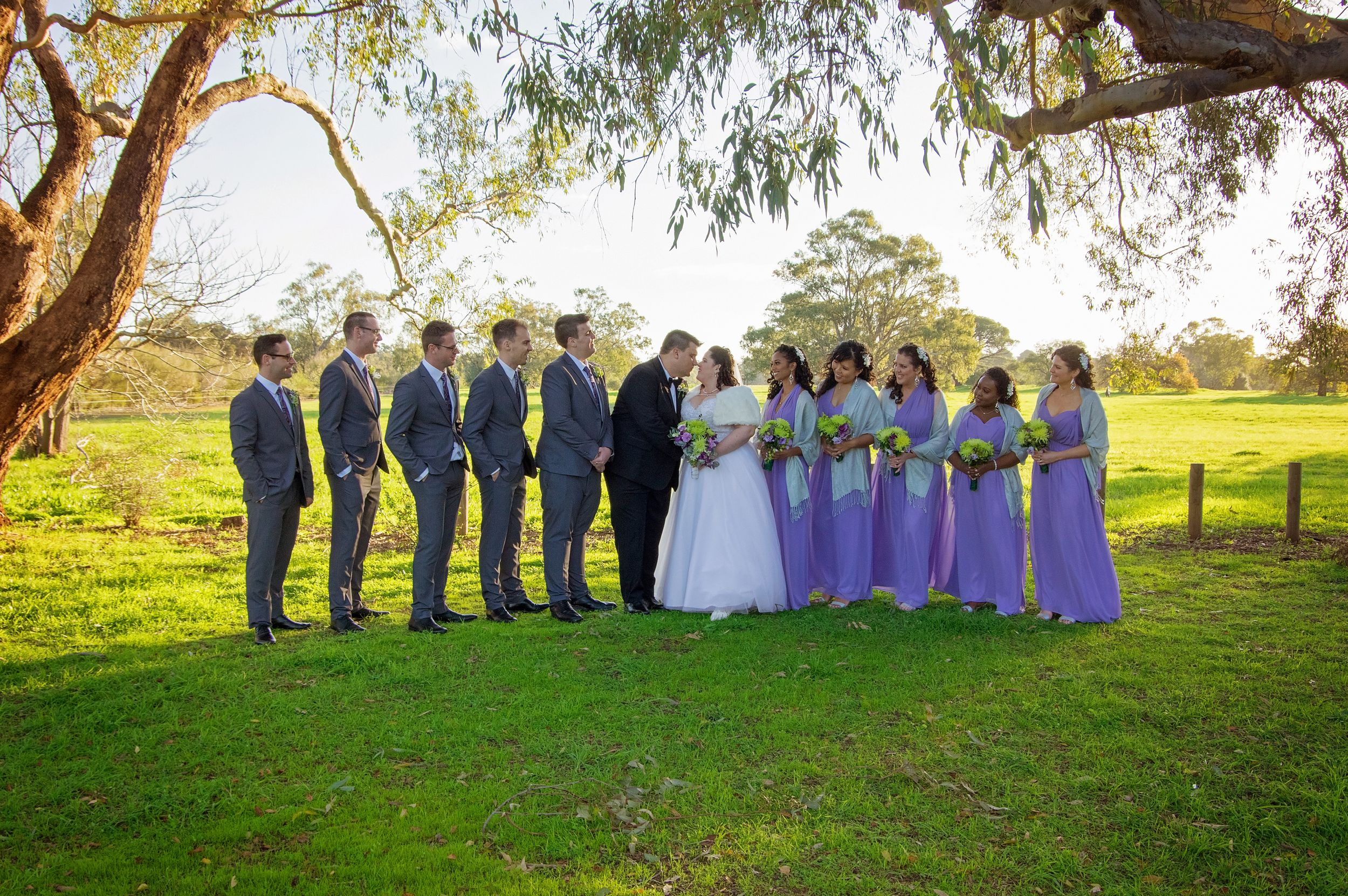 bridal party in grey and purple smiling at bride and groom