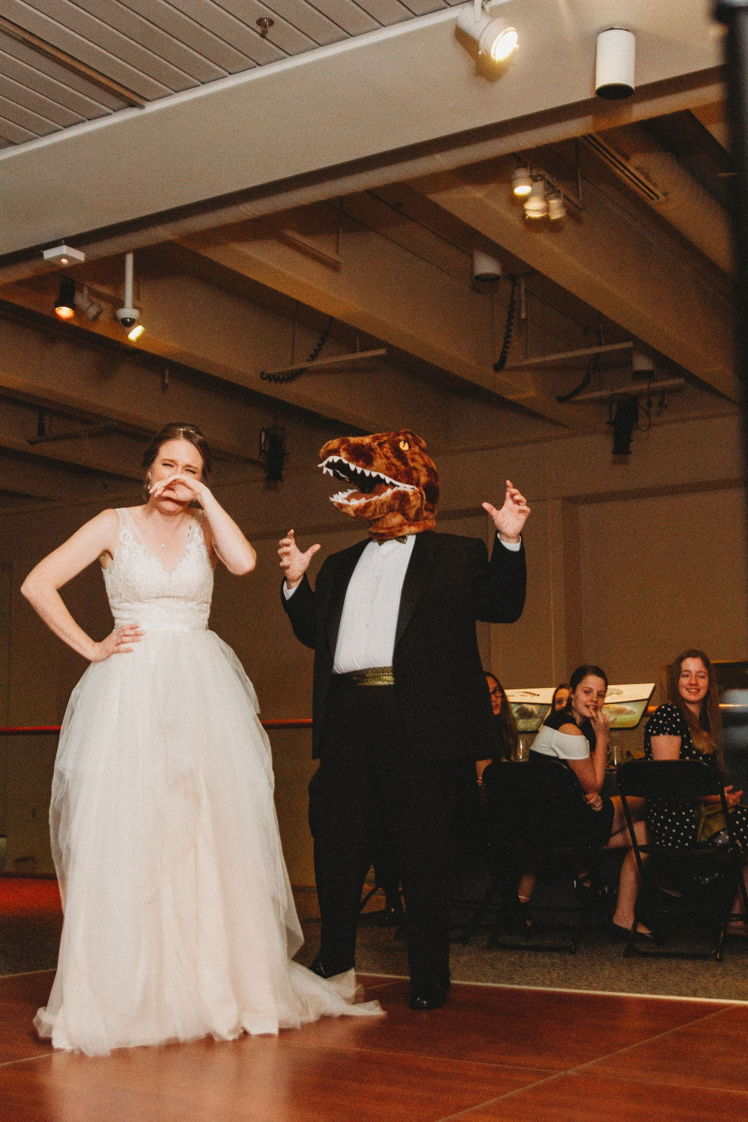 father of the bride in dinosaur head dances with his daughter after exchanging of vows