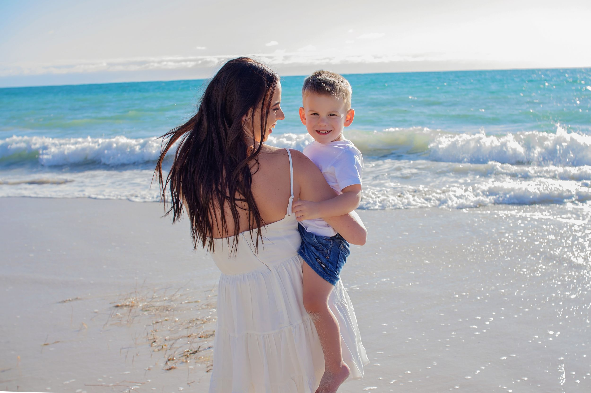 mother holding yougn son smiling on beach
