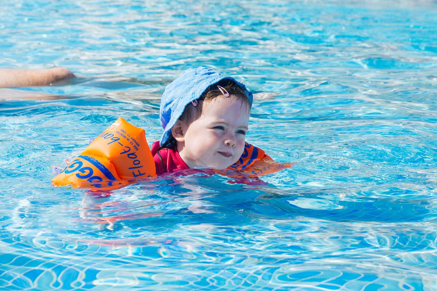 toddler girl swimming in pool with orange armbands