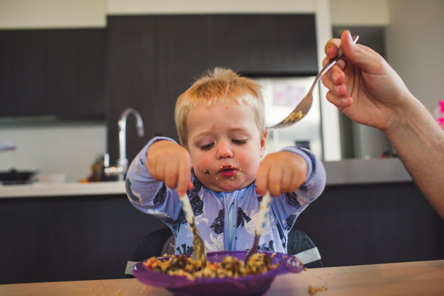 Toddler trying to eat his dinner