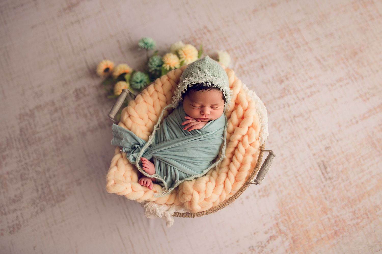 newborn baby girl with bonnet wrapped in a basket teal