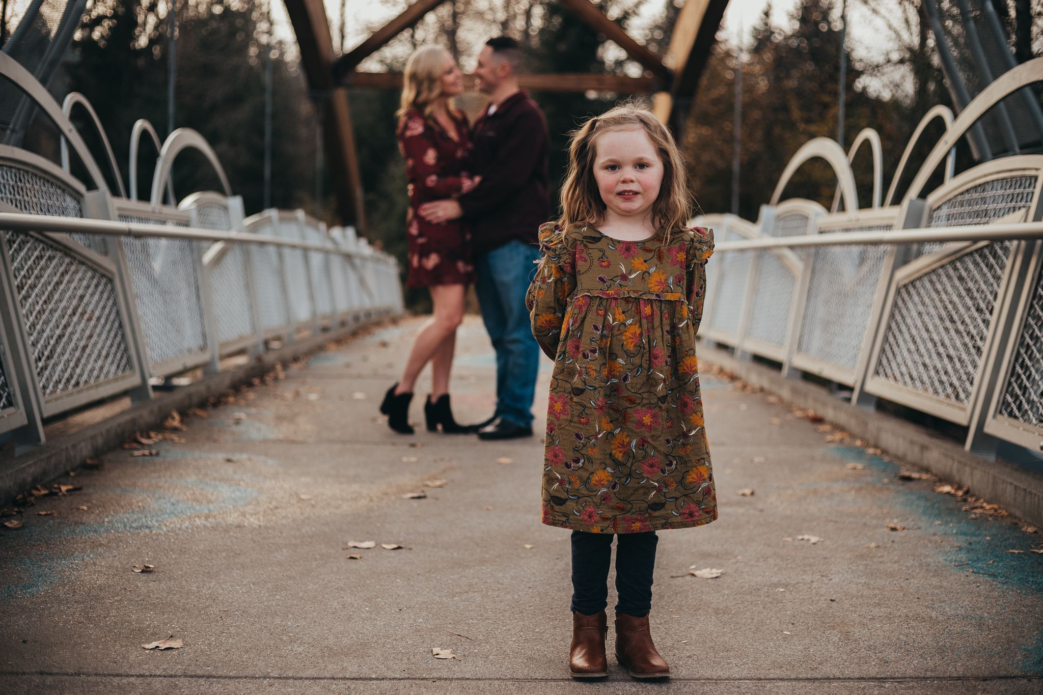 little girl standing in front of mom and dad on a bridge