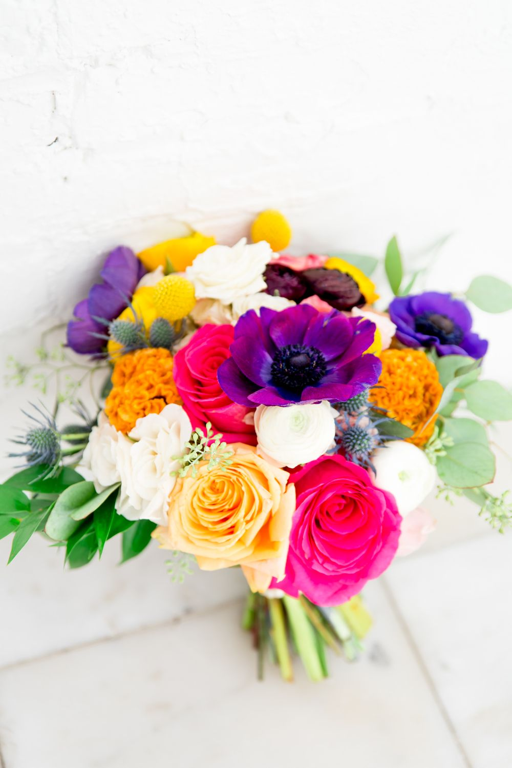 bright pink purple orange and white wedding bouquet against white wall at Room 1520