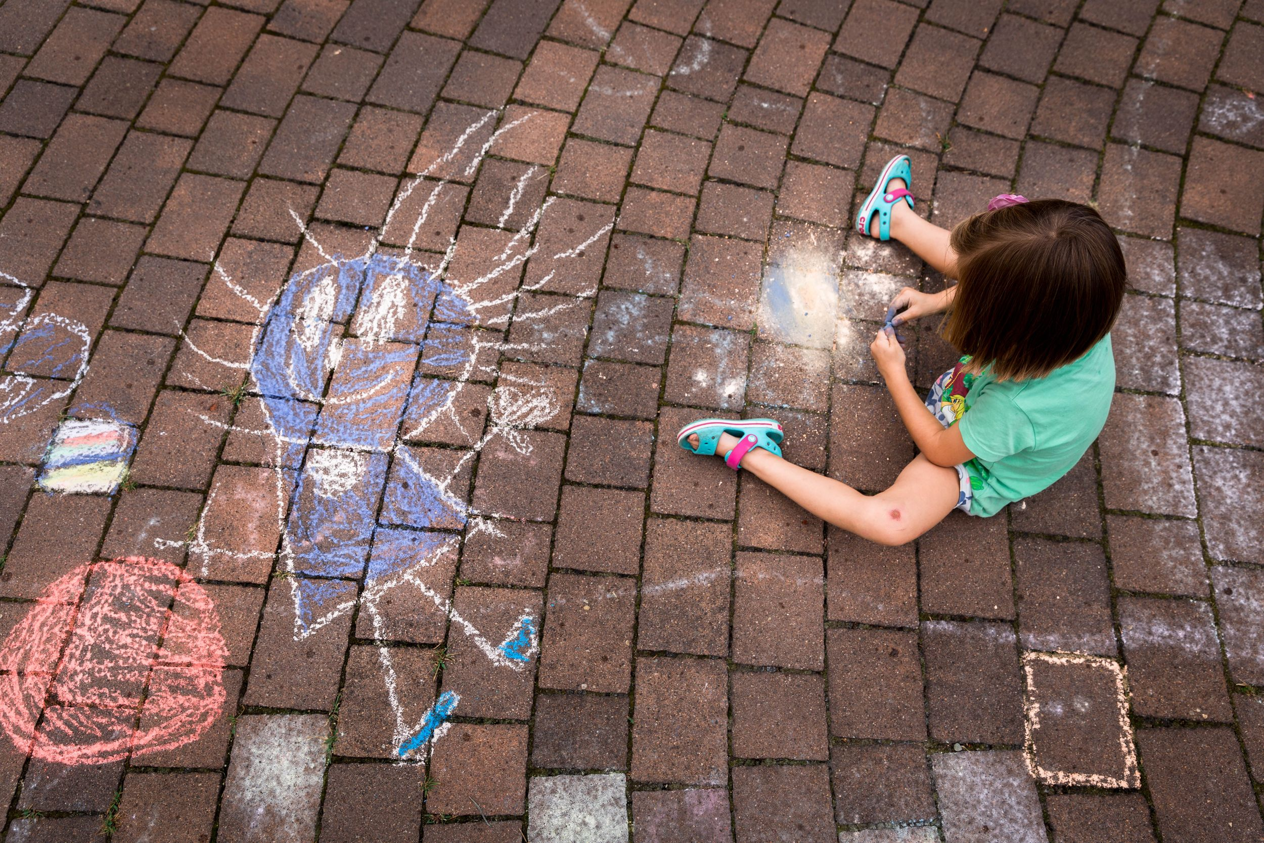 girl in green t-shirt sitting on floor drawing with chalk