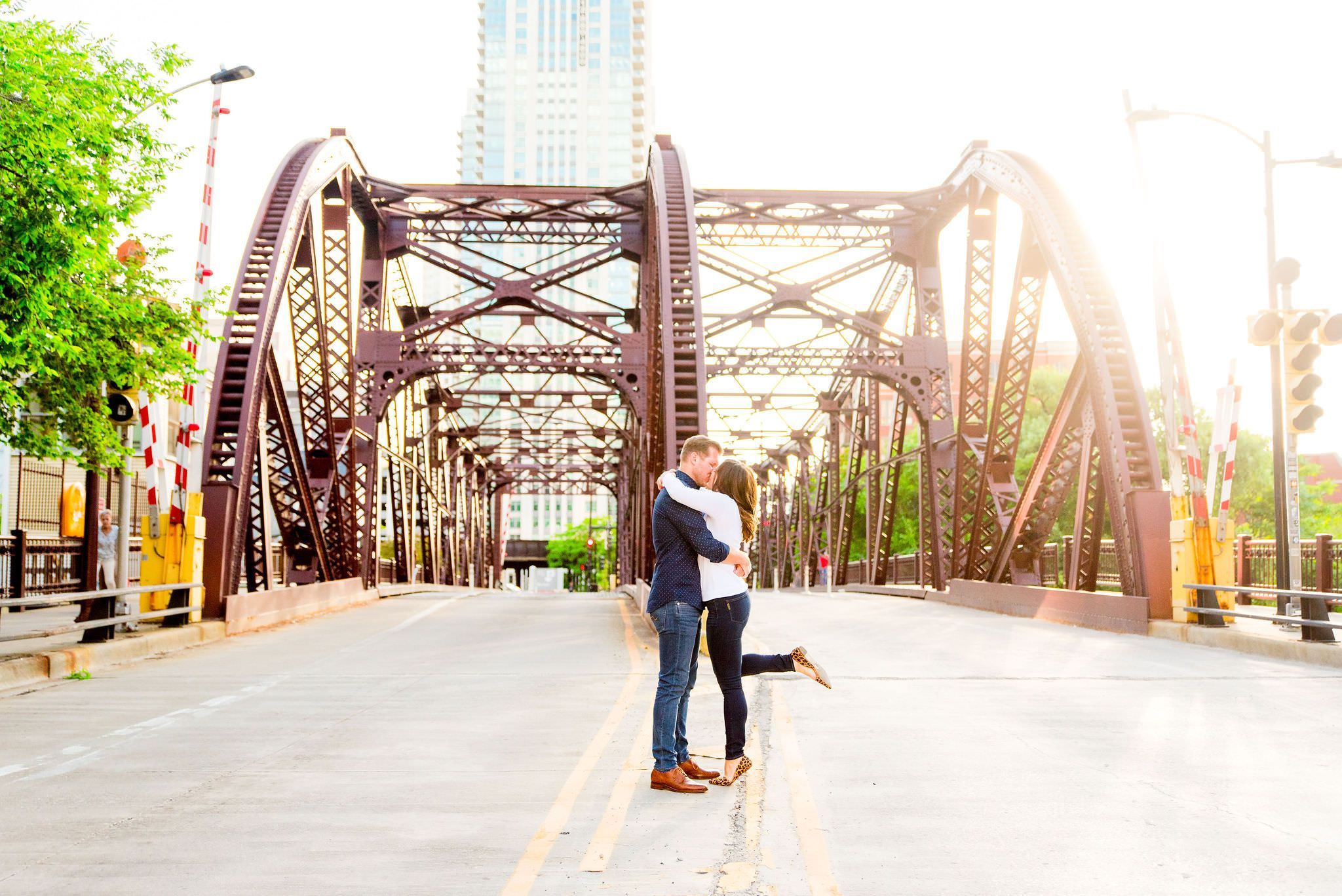 man and woman kissing in front of Kinzie St Bridge with her one leg up in leopard flat