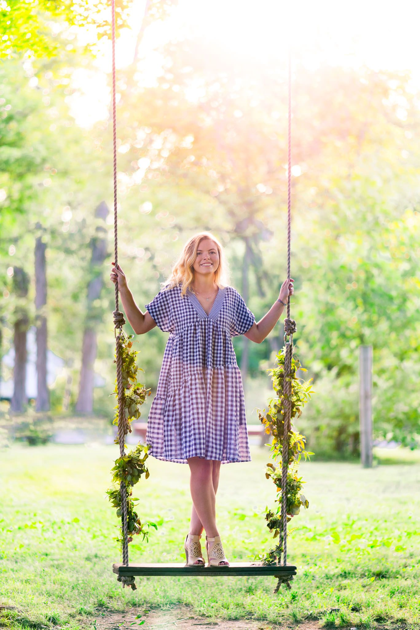 senior picture of a young woman in blue and white dress standing on a swing with floral ropes at sunset