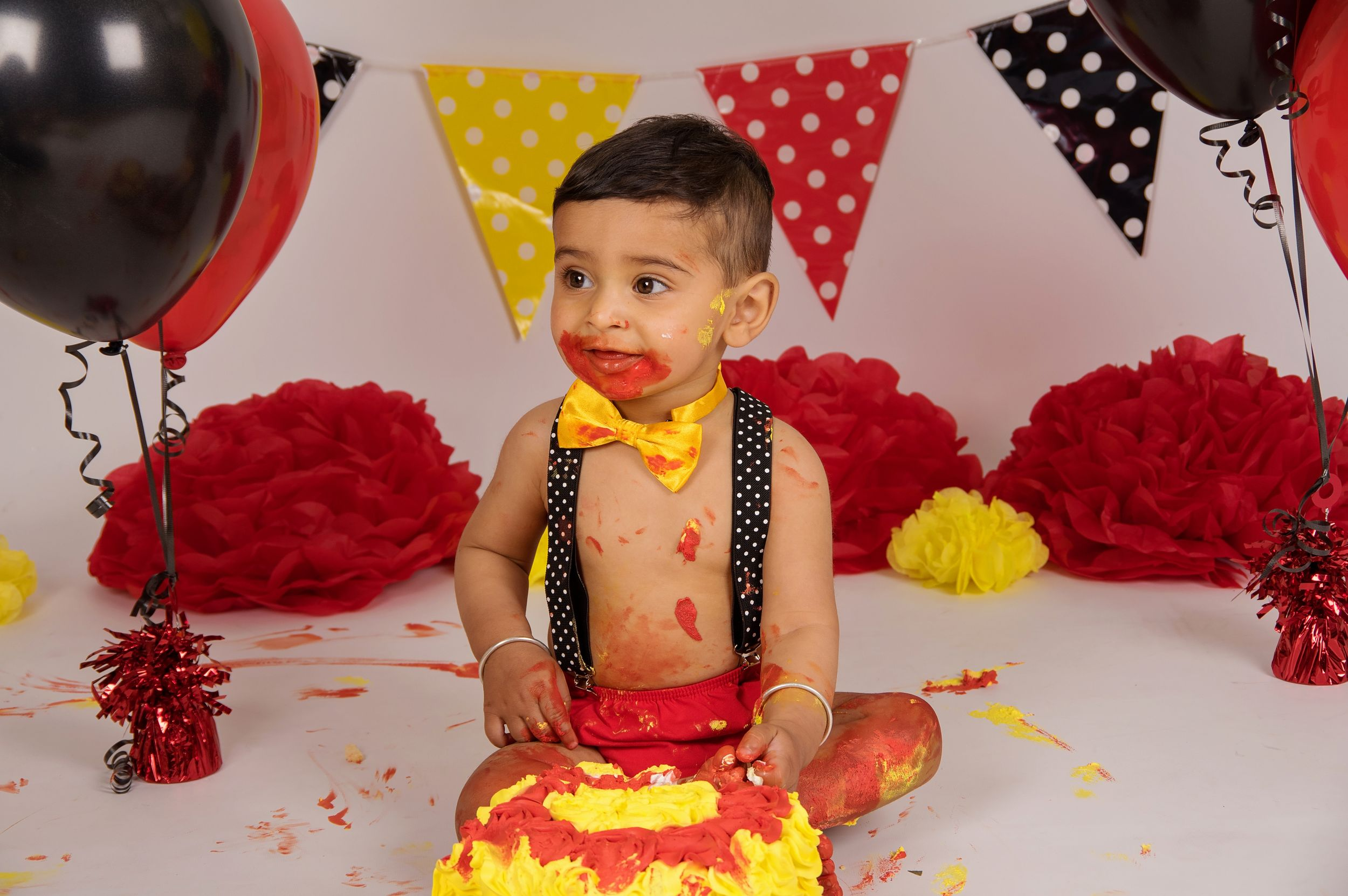 baby eating cake with mickey mouse decorations and balloons