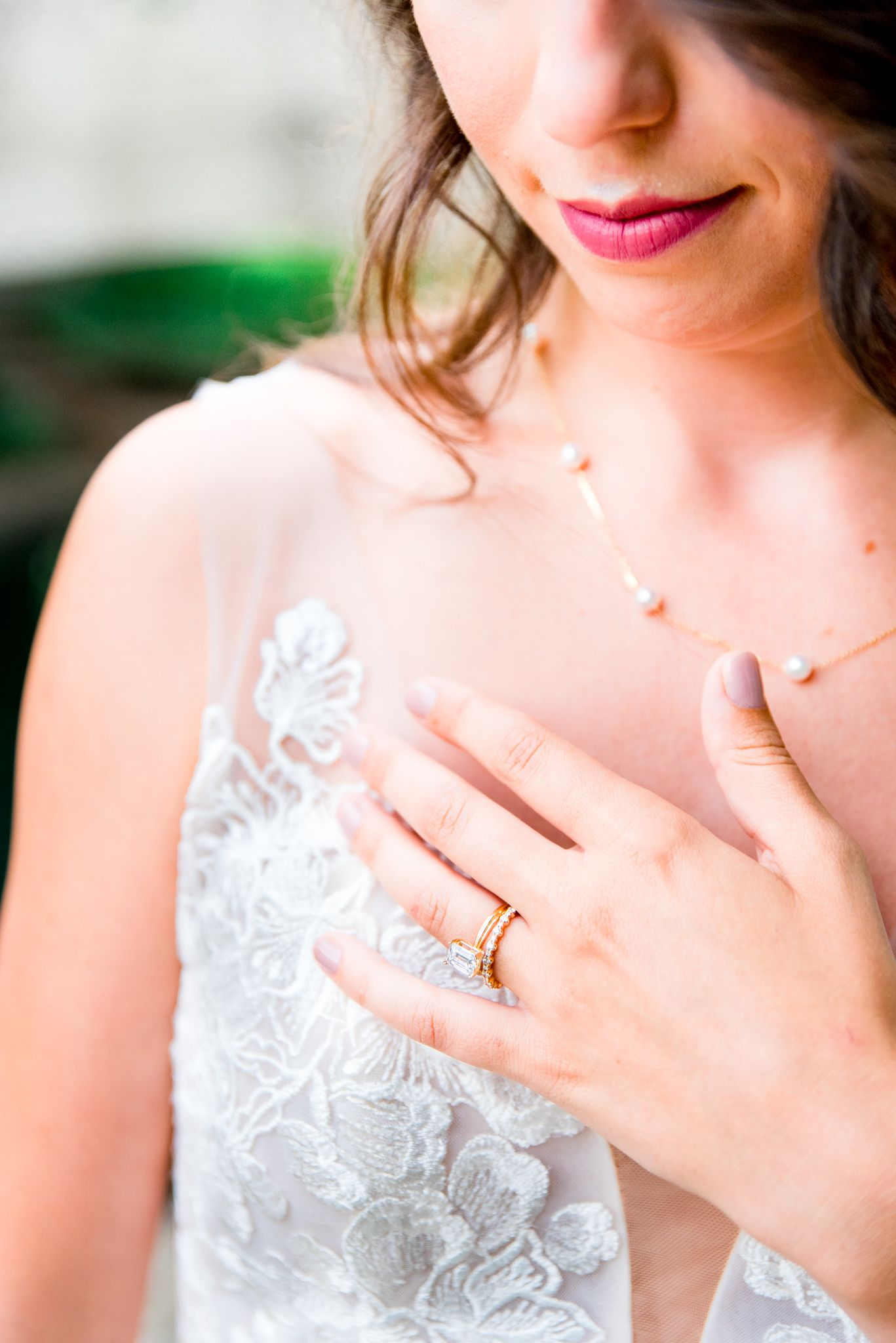 details of bride's lipstick, wedding dress, necklace, and engagement and wedding rings