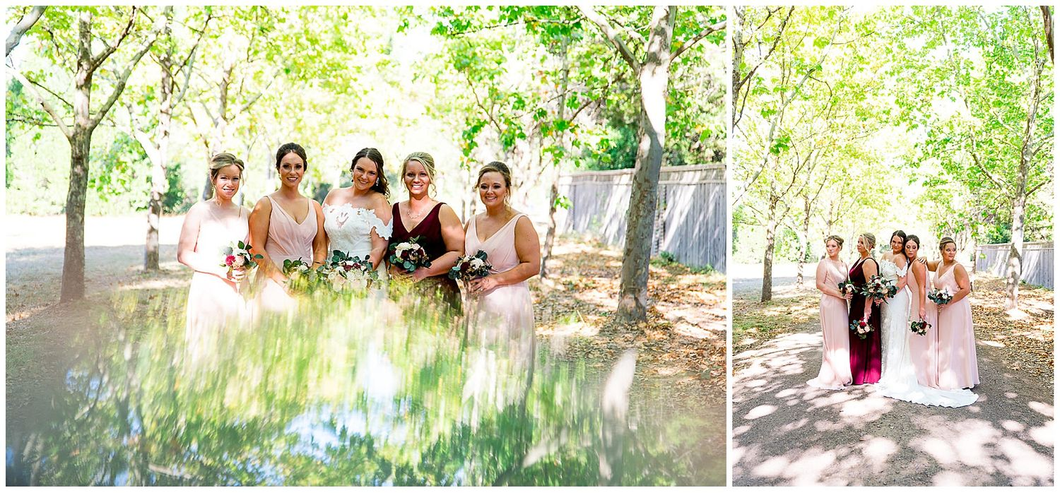 bride and bridesmaids smiling in a path of trees wearing blush and red for a September wedding in Northern California