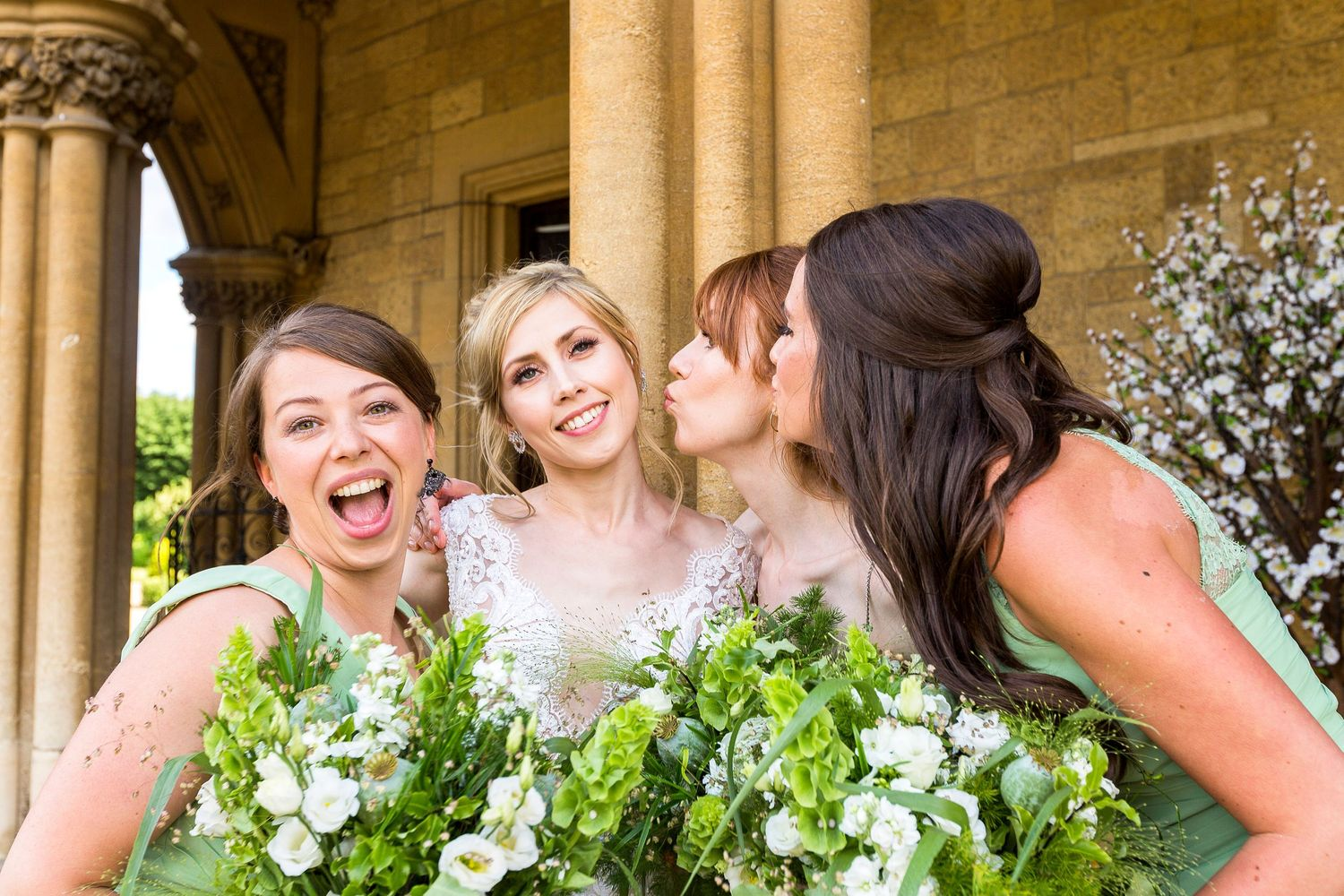 three bridesmaids close to bride blowing kisses all laughing