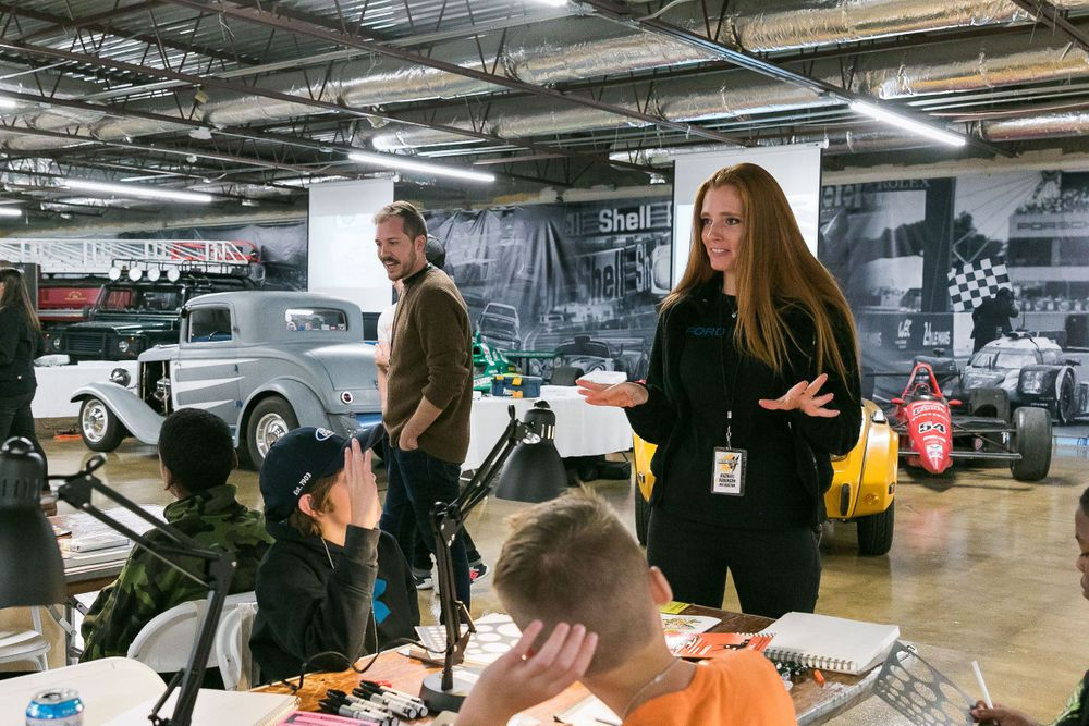 Woman car designer addressing a group of boys preparing to draw.