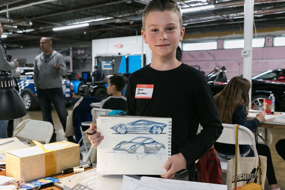 Young boy smiling and holding up a car design he created.