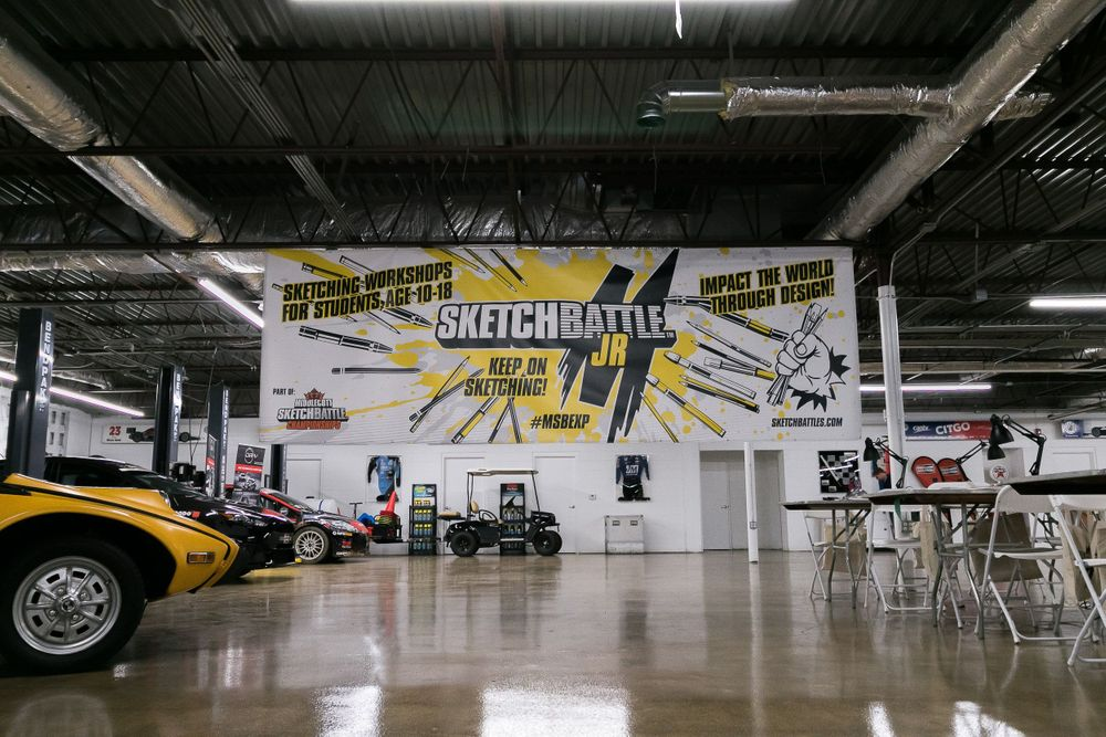 Low angle view of a commercial garage turned into an event space with a Sketchbattle JR banner hanging overhead.