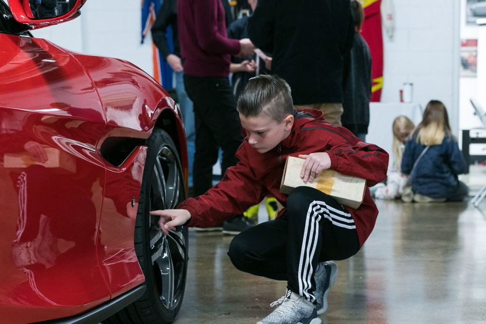 Young boy kneeling and checking out the tires on a car.